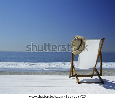 View of a lawn chair on a deck overlooking the beach