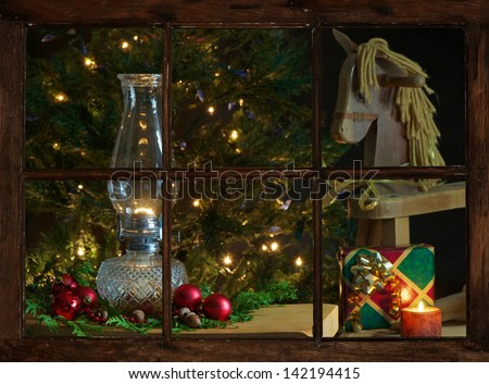 View of a living room decorated for Christmas, as seen through the farmhouse window at night.