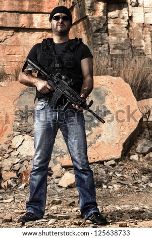 Stock Photo View of a man with a machine gun in jeans and jacket on a stone quarry.