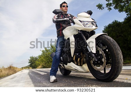 View of a man with a motorcycle on a asphalt road.