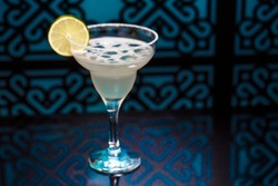 View of a Margarita Coctail in blue font, with a lemon slice on the edge of the glass. Colourful coctail on the black background