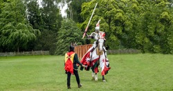 View of a medieval knight and horse in armour and costume ready for jousting