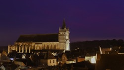 View of a medieval village in France at nightfall. The 11th century Romanesque church dominates the town. Dark sky, houses and streets are lit up. View of the rooftops seen from above