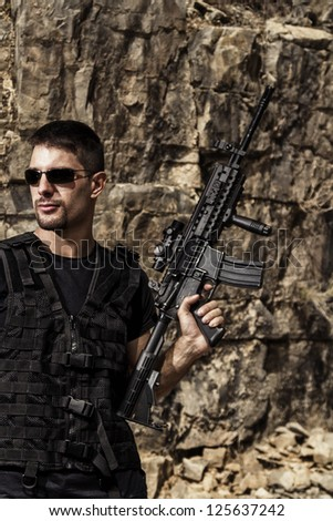Stock Photo View of a menacing man with a machine gun in a black shirt and dark shades on a stone quarry.