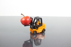 View of a miniature figure scene where a forklift is transporting an apple. Light background. Concept: modern food
