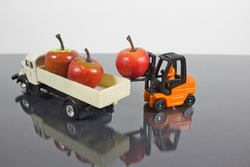 View of a miniature figure scene where a forklift truck transports an apple to load a truck. Light background. Concept: modern food
