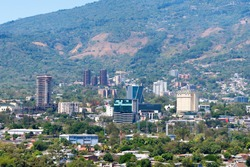 View of a modern part of San Salvador city, the capital of El Salvador in Central America. Commercial and residential buildings in a hill with lots of vegetation around. Upscale neighborhood.