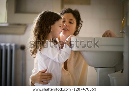 View of a mother and a daughter washing their hands. #1287470563