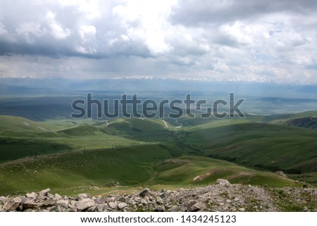View of a mountain valley with mountain ranges on the horizon against a cloudy sky. Traveling in Kyrgyzstan #1434245123