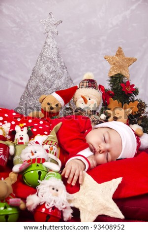 View of a newborn baby on a Christmas suit with stuffed toy.