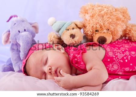 View of a newborn baby on smooth bed with stuffed toy sleeping.