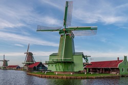 View of a number of working windmills situated on the bank of the river Zaan, in the middle of a few buildings that serve as workshops. Background a beautiful colored sky,