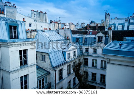 View of a Paris neighborhood skyline, featuring mostly rooftops from the top floor of an apartment building in Paris, France.