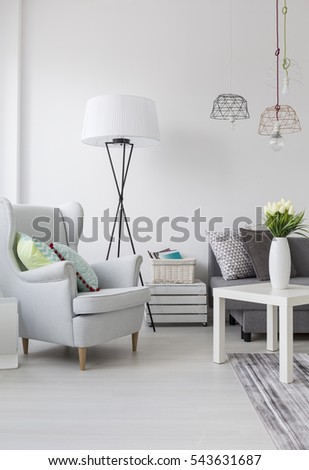 View of a part of a bright living room with a white armchair and lamp #543631687
