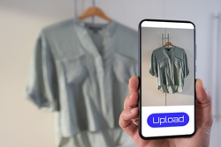 View of a person taking a photo of a blouse to upload in a second hand clothes app