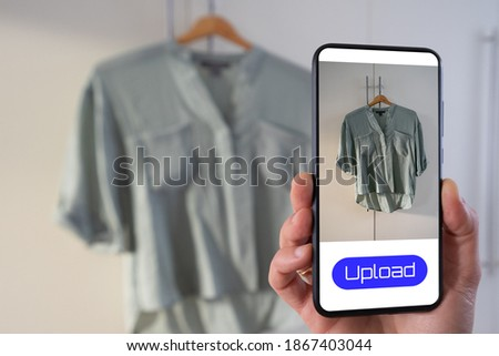 View of a person taking a photo of a blouse to upload in a second hand clothes app Foto stock ©