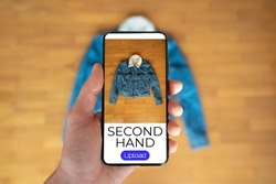 View of a person taking a photo of a jacket to upload in a second hand clothes app