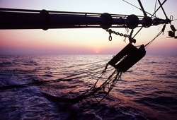 View of a prawn trawler boom arm with otter boards and bottom trawling nets at sunset on the fishing grounds in the Timor Sea of the north west coast of Darwin