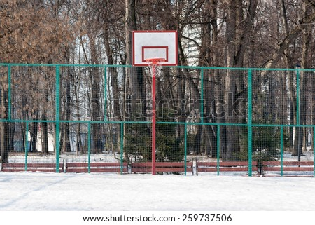 View of a public basketball court in wintertime. The court is covered with snow, no players, just a lonely backboard. But the warm season is nearing and the court will be actively used.