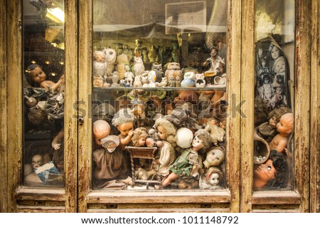 View of a puppet store window, full of old, dusty toys. The photo transmits a strong feeling of nostalgia, after all the passed childhoods.