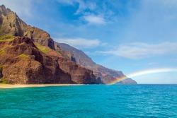 View of a rainbow off of Kauai's rugged Nā Pali Coast, where Kauai's rugged, remote coastline meets the Pacific Ocean