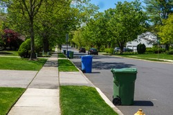 View of a residential tree lined street with green and blue trash bins lined up along the curb for trash truck collection.