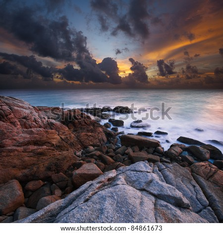 View of a rocky coast at sunset. Ultra-wide angle, long exposure shot.