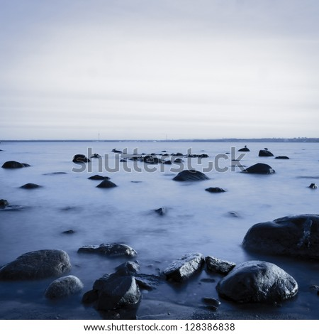 View of a rocky coast in the evening. Long exposure shot. Black and white image