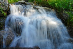 View of a running waterfall over boulders in the Laurance S. Rockefeller Preserve, a nature refuge on Phelps Lake in Grand Teton National Park in Jackson, Wyoming, United States