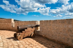 View of a rusted cannon at Saint Mary's Battery (Il-Batterija ta' Santa Marija). A beautiful historic old artillery battery from the 18th century on the island of Comino in Malta on a sunny day.