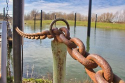View of a rusted iron post through which a rusted steel chain is panned as a handrail by an iron ring at the top. In the background a boat harbor on the Rhine near Cologne