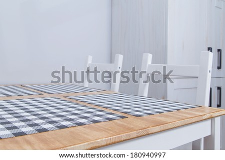 View of a rustic kitchen table with white chairs