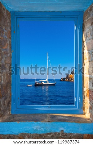View of a sailing boat threw a window  in Santorini island Greece