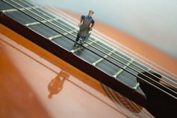 View of a section of an acoustic guitar where a miniature figure pulls a handcart behind it and walks over the guitar strings. White background