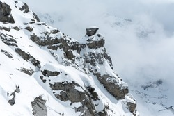 View of a section of the mountain as fog rises and covers the peak of Mount Titlis in Engelberg, Switzerland. Snowcapped peaks.