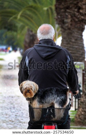 View of a senior man walking on a bicycle with is pet dog.