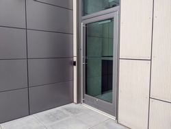 View of a side entrance door for a business building with a keyless entry box on the side.