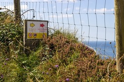View of a sign from Liscannor Burren Way walking trail in County Clare Ireland with nature and Atlantic Ocean in background