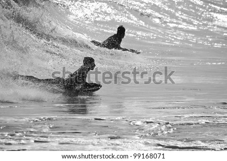 View of a silhouette of a boy surfin' the waves.