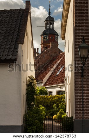 View of a small street and church in the Dutch city Buren.