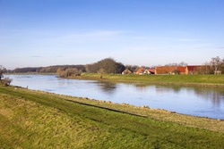 View of a small village directly behind the dyke of the river Elbe. The dike is the most important protection against flooding. The houses show the typical north German brick construction.