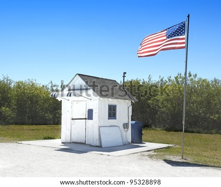 View of a small wooden building, serving as the smallest post office in America, with the American Flag