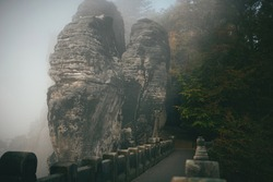 view of a stone ancient bridge in the rocks in autumn and a mystical foggy atmosphere around