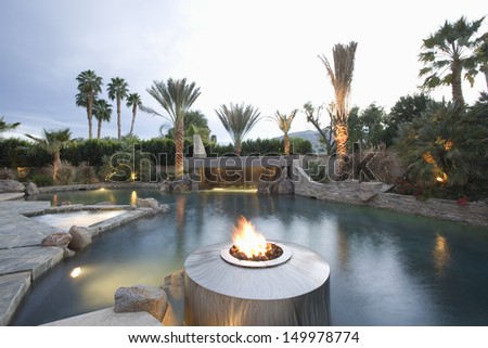 View of a swimming pool with live flame heater in foreground