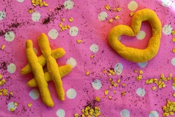 View of a table with different shaped breads: euro, dollar, heart, at, hashtag on a pink tablecloth with white polka dots that symbolizes the relationship between food, the economy and technology