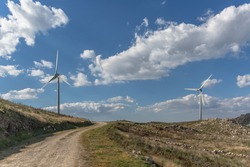 View of a top mountains landscape with a wind turbines, green herb fields and dirty road, cloudy sky as background
