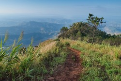 view of a tourist walking down hill on trail way around with green grass and the hill with blue sky background, Phu Nom, Phu Langka Forest Park, Phayao, Thailand.