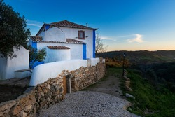 View of a traditional house painted in white and blue, with agricultural fields on the background, near Mafra, Portugal.
