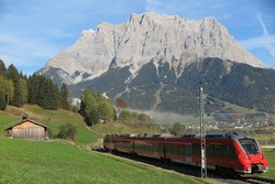 View of a train traveling through green fields with Mountain Zugspitze in the background on a beautiful sunny day in Lermoos, Tirol Austria ~ Magnificent summer scenery of idyllic Tyrolean countryside