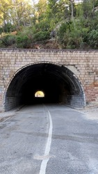 View of a tunnel in a mountainous area, a highway through a tunnel surrounded by coniferous thickets